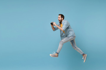 Cheerful traveler tourist man in yellow casual clothes with photo camera isolated on blue background. Male passenger traveling abroad on weekend. Air flight journey concept. Jumping, taking pictures.
