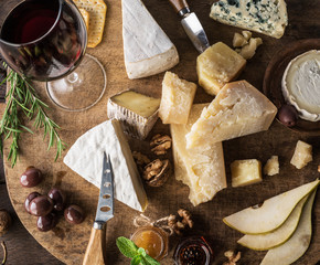 Wall Mural - Cheese platter with organic cheeses, fruits, nuts and wine on wooden table. Top view. Tasty cheese starter.