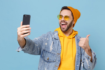 Funny young hipster guy in fashion jeans denim clothes isolated on pastel blue background. People lifestyle concept. Mock up copy space. Doing selfie shot on mobile phone, showing thumb up, blinking.