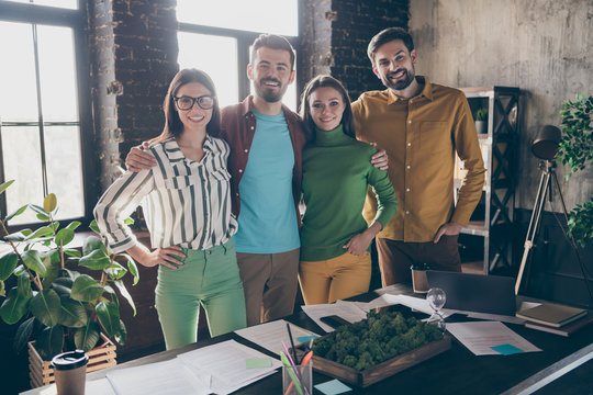 Company of four nice attractive friendly professional cheerful cheery people leaders partners IT specialists hugging support corporate climate at work place station office indoors
