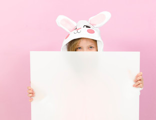 pretty blonde girl with cozy rabbit costume and white sign is posing in the studio