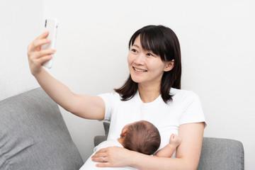赤ちゃんを抱いてスマートフォンを使う女性