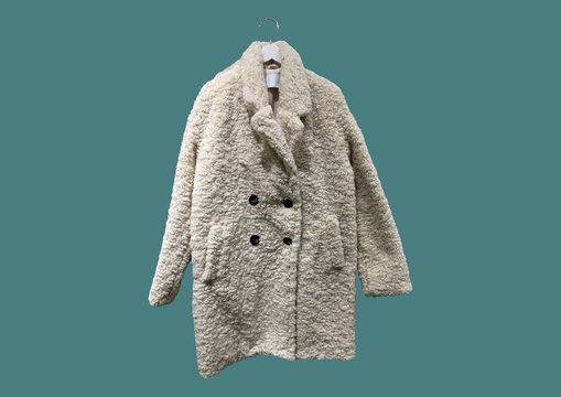 Fashionable white women Faux shearling coat on a hanger isolated on green background.  Composition of clothes. Flat lay, top view, copy space. Winter clothes pattern. Ladies' Trench Coat. Pattern