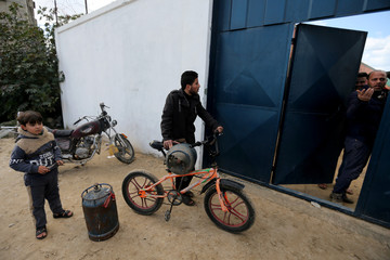 Palestinians wait to fill cylinders with cooking gas in Rafah in the southern Gaza Strip