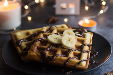 Viennese waffles on a plate with banana and chocolate. In the background are lights and candles. Romantic picture