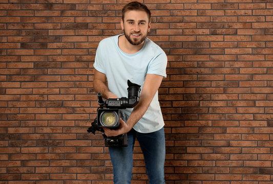 Operator with professional video camera near brick wall