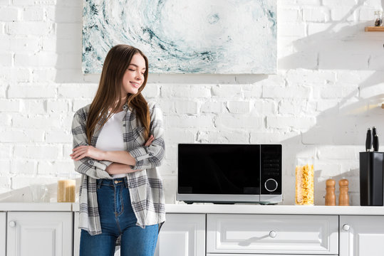 smiling and attractive woman standing near microwave in kitchen