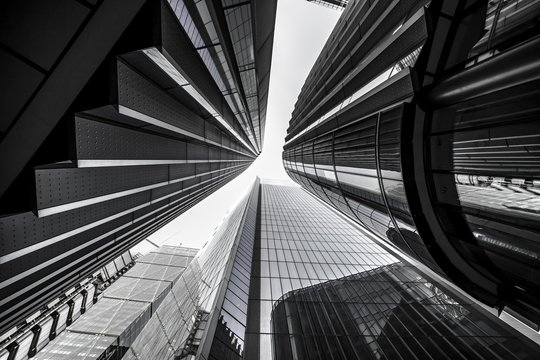 Low angle greyscale of modern skyscrapers with glass windows under sunlight