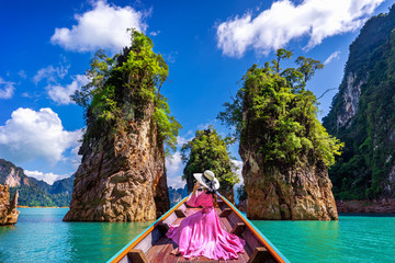 Wall Mural - Beautiful girl sitting on the boat and looking to mountains in Ratchaprapha Dam at Khao Sok National Park, Surat Thani Province, Thailand.
