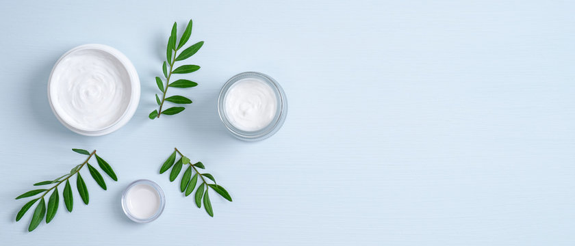 Jars of organic cosmetic cream and green leaves on blue background. Organic natural cosmetic products. Skincare, body care, SPA treatment concept. Banner mockup for eco shop or beauty salon