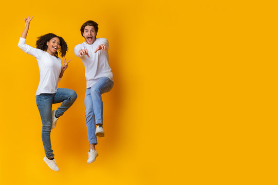 Funny Interracial Couple Jumping In Air On Yellow Background In Studio
