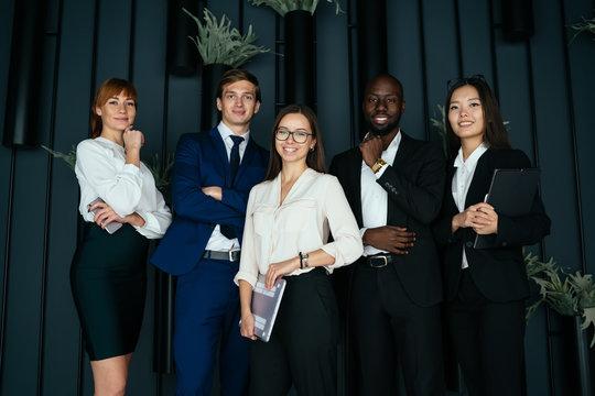 Joyful multiethnic colleagues in contemporary office