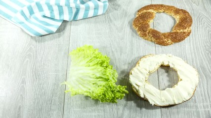 Fototapete - making bagel sandwich with cream cheese, lettuce, tomato, ham. step by step. time lapse. close up