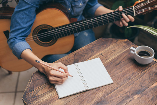 artist songwriter thinking writing notes,lyrics in book at studio.man playing live acoustic guitar relax chill.concept for musician creative.composer work process.people relaxing time with instrument