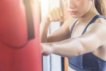 Asian woman in sports bra punching red sandbag without boxing glove.