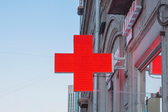 """NOVOSIBIRSK, RUSSIA - APRIL 29, 2018: Medical red cross with russian text """"PHARMACY"""" on the building. Concept medical help."""