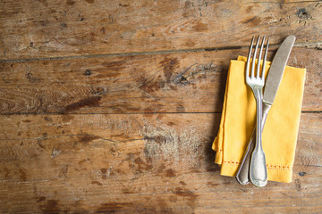 Table setting with antique fork and knife, yellow linen napkin on old wooden background. Space for text, flat lay
