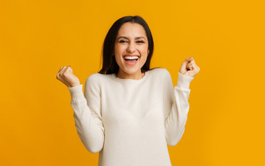 Ecstatic hispanic girl emotionally celebrating success over yellow background