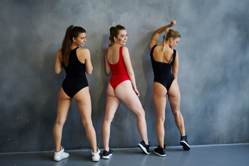 Female gymnasts posing for picture next to studio wall