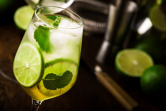 Mojito cocktail with lime and mint in wine glass on wooden background. Copy space