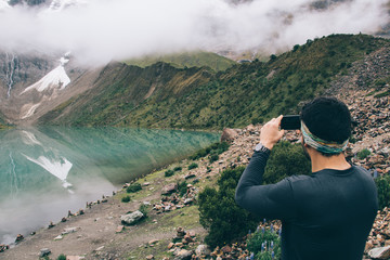 Male in active wear using smartphone technology with image application for creating wonderful multimedia content of water reflection of high mountains, man clicking pictures during trekking adventure