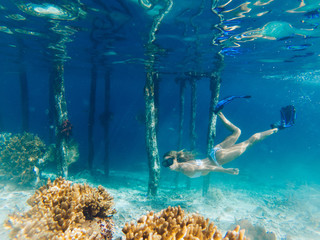 Freedom lifestyle and aquatic underwater life on Raja Ampat island of New Guinea, active woman in swim mask and flippers enjoying summer scuba diving in blue ocean with beautiful coral reef Wall mural