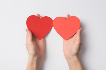 partial view of woman holding blank red heart shaped hearts on white background