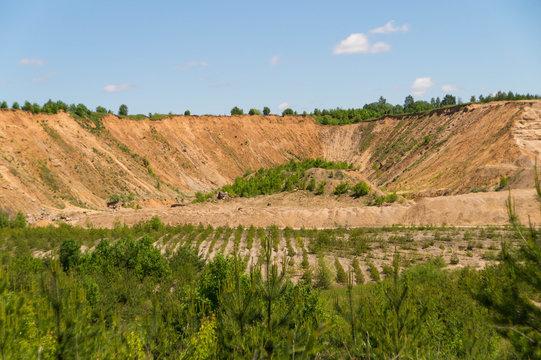 Landscape: inactive abandoned overgrown sand quarry under a blue sky