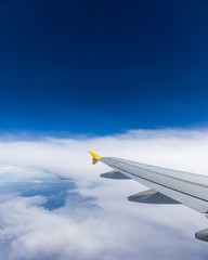 View of the wing of an airplane flying above the clouds at high altitude under a blue sky from the passenger window. In flight over Europe. View of jet airplane wing flying in blue sky over clouds.