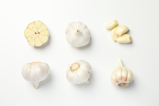 Flat lay with garlic bulbs on white background, top view