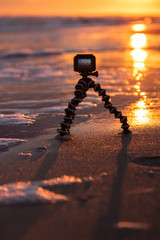 An action camera capturing a time lapse video of a beautiful sunset on a pristine beach.