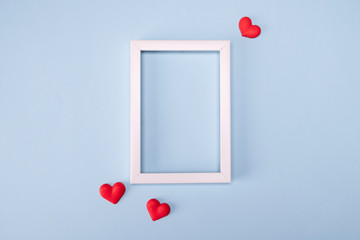 Minimal valentine day concept. White empty photo frame with hearts on blue background. Flat lay, top view, copy space . Template for greeting card, seasonal promotions and discounts