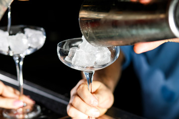 Bartender adds ice to cocktail.