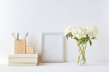 Home interior with decor elements. White frame, white peonies in a vase, interior decoration