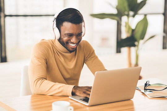 Smiling african american businessman chatting online at work