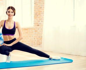 Happy smiling brunette girl in sportswear, doing fitness exercise, indoors. Healthy lifestyle, weight lossing and sporting theme concept.