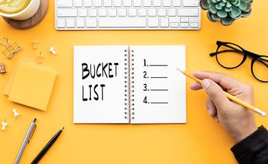 Youngman writing bucket list on notepad