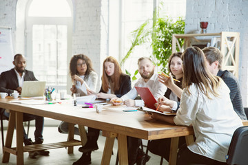 Best team. Group of young business professionals having a meeting. Diverse group of coworkers discuss new decisions, plans, results, strategy. Creativity, workplace, business, finance, teamwork.