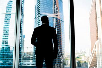 Businessman silhouette in office near window