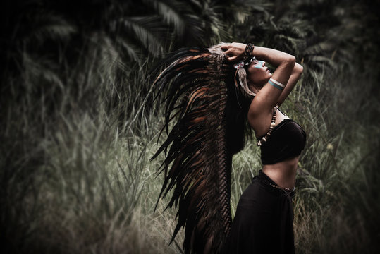 Portrait of beautiful woman posing in the wild forest.hold indian feather hat in hand.