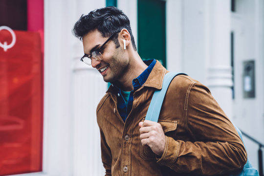 Ethnic young man with earbuds walking on street