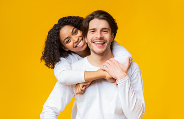 Young interracial couple in love cuddling and posing over yellow background
