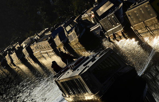 Late afternoon sunlight reflects off narrowboats and barges on Regent's Canal in London