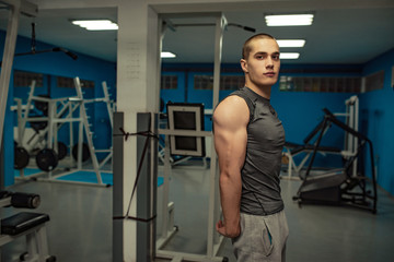 Fototapeta Handsome man with big muscles, posing at the camera in the gym