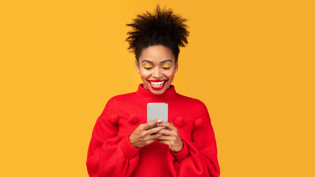 Smiling afro girl using cell phone at studio