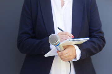 Woman reporter or journalist at media event, holding microphone, writing notes. Broadcast journalism concept.