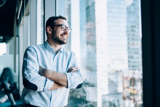 Cheerful male entrepreneur with crossed hands standing near office window view and smiling during work day in company, Caucasian successful corporate boss feeling good from wealthy lifestyle