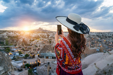 Wall Mural - Woman take a photo with her smartphone at Goreme, Cappadocia in Turkey.