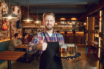 Bearded waiter with a tray of glasses of beer against the background of a pub bar