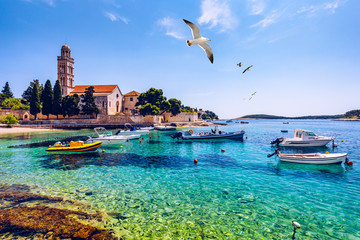 View at amazing archipelago with fishing boats in front of town Hvar, Croatia. Harbor of old Adriatic island town Hvar with seagull's flying over the city. Amazing Hvar city on Hvar island, Croatia. Fotomurales
